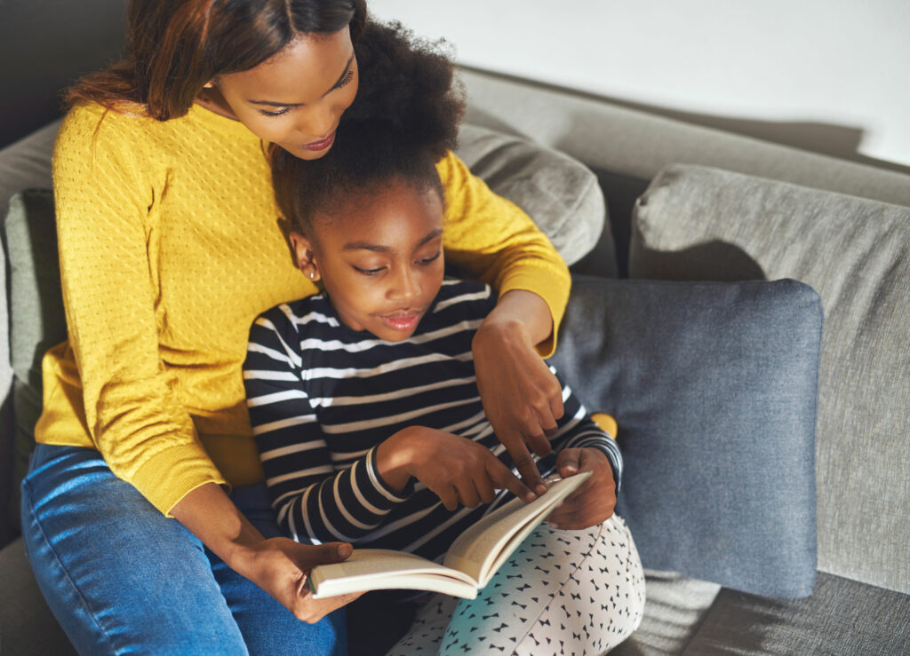 daughter learning how to read from mother