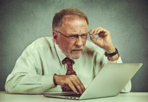 older man struggling to read on a computer